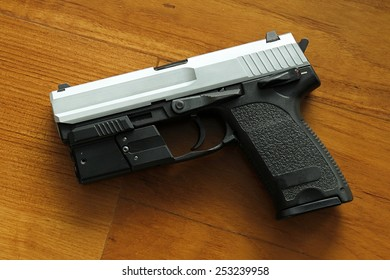 Semi-automatic handgun on wooden background, 9mm pistol.