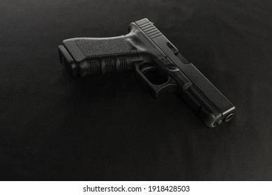 A semiautomatic handgun is set on a black background and view from above. The muzzle end of the barrel is facing the bottom right of the frame.
