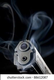 Semi-automatic handgun that is enveloped in smoke after a shot was taken