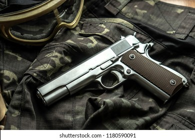 The semi-automatic silver pistol is placed on the military garb.