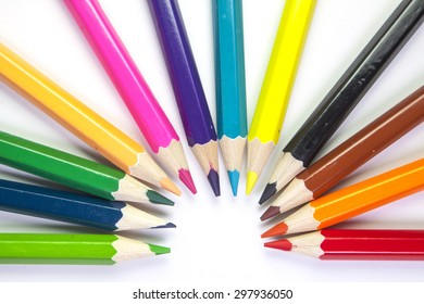 Semicircle of rainbow colored pencils on white background