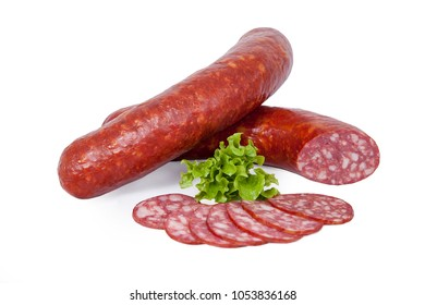 Semi-dry sausage with pieces of fat in natural shell. Meat product whole and partially sliced. Decorated with lettuce. Isolated on white background