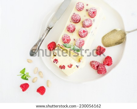 Semifreddo (italian cheese ice-cream dessert) with pistachios and fresh raspberries on a plate over a white background