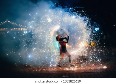 SEMIGORYE, IVANOVO OBLAST, RUSSIA - JUNE 26, 2018: Fire show. Girl spins fiery sparkling torches. Dangerous amazing night performance