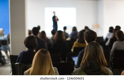 Seminar Audience in Training Room Watch Presentation. Speaker in Meeting at Business Event. Expert Presenter Giving Talk with Young Group of People. Rear View of Audience People Who Listen to Speaker.