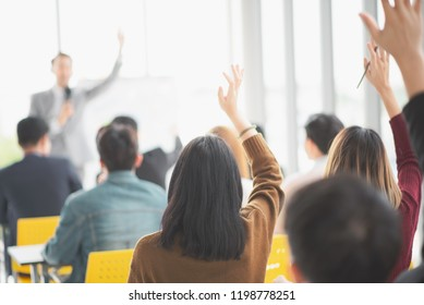 Seminar group raising up hand for asking the speaker that allow to raising up hand in question and answer time in meeting room back side