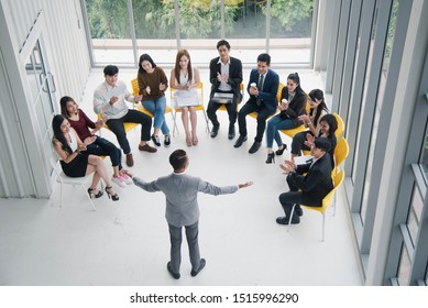 Seminar group, Successful young Asian business man and woman, the man speaker presenting to employees, business coach giving presentation to clients in meeting room, team leader reporting about work.