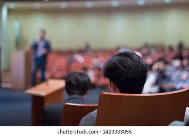 Seminar presenter at corporate conference giving speech. Speaker giving lecture to business audience. Executive manager leading discussion in hall during company training event.