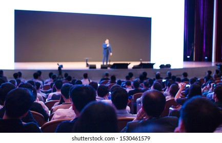 Seminar presenter at corporate conference giving speech. Speaker giving lecture to business audience. Entrepreneur forum executive manager leading discussion in hall during company training event.