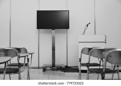 Seminar room where there is a TV monitor, a microphone on the podium and chairs for audiences. Black and white image of a seminar.