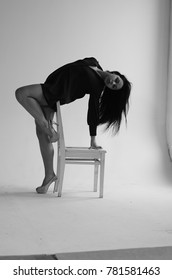 Semi-nude beautiful girl posing on a chair in a classic suit