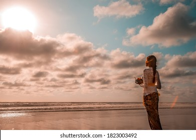 Seminyak, Bali, Indonesia - Dec 9 2018 : Young Balinese women pray in the beach in Bali in the sunset time wearing Balinese Traditional Dress