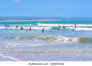 SEMINYAK, BALI ISLAND, INDONESIA - SEPTEMBER 8, 2018: Surfers on the famous Seminyak Beach - the best place to learning surfing.