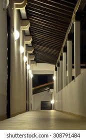 Semi-open corridor under a wooden roof, with a succession of the wall lamps on the left side, and columns on the right side. Corridors and passageways under artificial lighting (reprocessed image)