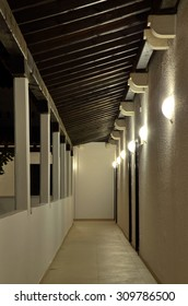 Semi-open corridor under a wooden roof, with a succession of wall lamps on the right side, and columns on the left side. Corridors and passageways under artificial lighting (reprocessed image)