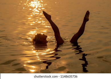 Semi-silhouette of a woman bathing in the ocean at sunset in Ouddorp, The Netherlands