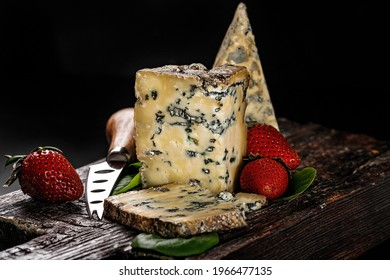 Semi-soft cheese with mold made from cows milk. The king of blue cheeses is Stilton. A piece of cheese and ripe strawberries on a dark wooden board and a cheese knife. Low key image. Copy space