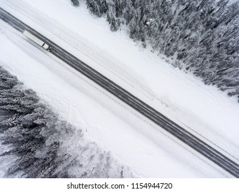 Semitrailer truck driving on winter blizzard asphalt road. Top view from drone