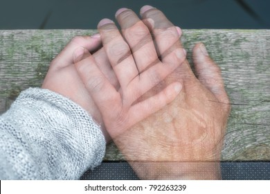 Semi-transparent man's hand on a woman's hand as a sign of farewell by separation or death