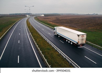 The semi-truck moving on a highway. The highway has multiple lanes on it and there is no other traffic. The truck is white. The truck is moving between painted white lines on the asphalt.