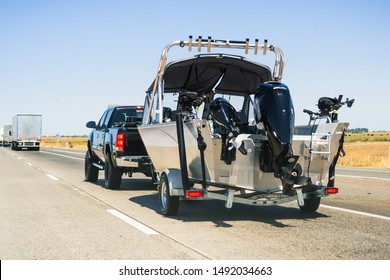 Semi-truck towing a  boat on the interstate, California