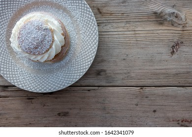 Semla is a bun filled with almond paste and whipped cream, served on a rustic table.