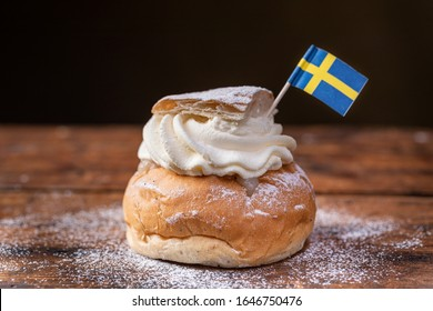 Semla, fastelavnsbolle, fastlagsbulle. A traditional scandinavian cream filled cardamom bun with almond paste. Decorated with a swedish flag. On a wooden table with dark background.