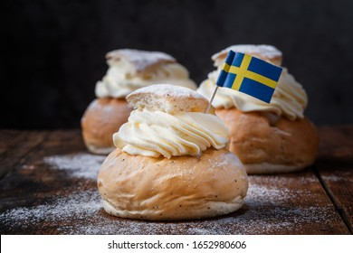 Semlor, fastelavnsbolle, fastlagsbulle on dark background.  Traditional scandinavian cream filled cardamom buns with almond paste.  Decorated with a Swedish flag.Horizontal view on an old wooden table
