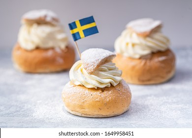 Semlor, fastelavnsbolle, fastlagsbulle.  Traditional scandinavian cream filled cardamom buns with almond paste.  Decorated with a swedish flag. Horizontal view on a gray background.