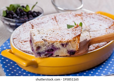 Semolina cake with berries, slice on a wooden spatula