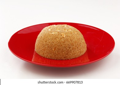 Semolina halva on a red plate, isolated on white