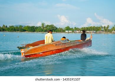 SEMPORNA ISLANDS BORNEO - MAY 12 2019; Orange boat with man and sons speeding across bay May 12 2019 Semporna Borneo