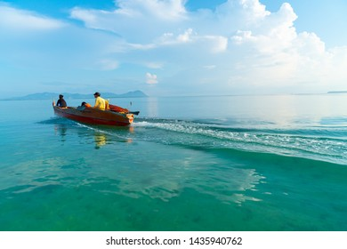 SEMPORNA ISLANDS BORNEO - MAY 12 ; Orange boat with man and sons crossing bay heading into open May 12 2019 Semporna Islands Borneo