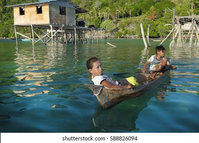 SEMPORNA, MALAYSIA - FEB 27 2017; Skillful sea Gypsy kid and friend in wooden boat ,canoe called lepa-lepa. The Bajau Laut are the sea gypsies who live in the open sea with beautiful scenic view .
