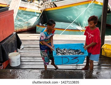 Semporna, Malaysia - June 13, 2019 : 2 young boys carry fish at fish market. Semporna is a gateway to nearby diving locations such as Sipadan and is a popular destination for fresh caught seafood.