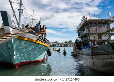 Semporna, Malaysia - June 13, 2019 : 2 small boats in between 2 fishing trawlers comes to shore. Semporna is a gateway to nearby diving sites and is a popular destination for fresh caught seafood.