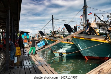Semporna, Malaysia - June 13, 2019 : A fisherman throws an empty basket to the fishing trawler after offloading. Semporna is a gateway to nearby diving sites and a popular destination for seafood.