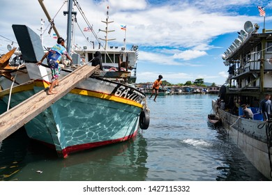 Semporna, Malaysia - June 13, 2019 : A young boy jumps from a fishing trawler while another embarks. Semporna is a gateway to nearby diving sites and a popular destination for fresh caught seafood.