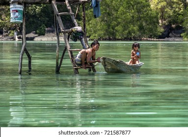 Semporna, Malaysia June 2015: Bajau tribal Mother bathing her little daughter who is sitting in a small boat, Sabah Semporna, Malaysia