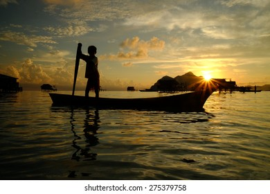 SEMPORNA, SABAH, BORNEO - APRIL 18 : Unidentified kids paddle a dug out boat on APRIL 18, 2015 in Semporna, Sabah, Malaysia. They inhabit villages built on stilts in the middle of ocean.