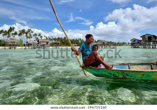 SEMPORNA SABAH, MALAYSIA - APRIL 19, 2015: Young girl of Bajau laut paddling a boat near Bajau Laut village in Maiga Island in Semporna, Sabah Borneo, Malaysia.The Bajau Laut are nomadic sea gypsies.