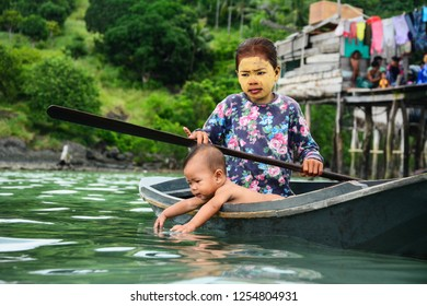 Semporna Sabah Malaysia - Dec 17, 2017: A sea gypsy girl wearing homemade face mask with her baby sibling rides in a wooden canoe. Sea gypsy people are known for building stilt houses at the sea.