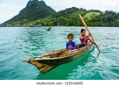 Semporna Sabah Malaysia - Dec 17, 2017: A sea gypsy woman with her son rides in a wooden canoe at Bodgaya island. Semporna has many beautiful islands famous for tourist attractions.