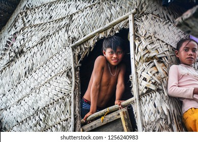 Semporna Sabah Malaysia - Dec 17, 2017: Two sea gypsy siblings looking at camera at their stilt house built from nipa palm leaves. Sea gypsy people of Semporna known for building their house on water.