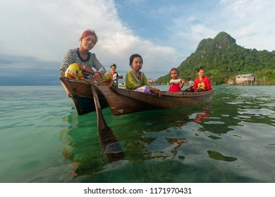 Semporna Sabah Malaysia - Sep 1, 2018 : Group of Sea Bajau ladies on wooden boat with Bodgaya Island peak at their backgrounds . Stateless Sea Bajau mainly reside around island of the Celebes Sea.