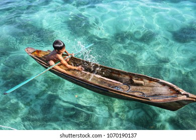 Semporna Sabah, Malaysia-September 17, 2011: Young Sea Gypsy  rowing wooden boat with clear crystal water.