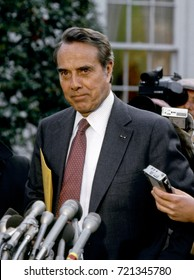 Senator Robert Dole Republican from Kansas talks with reporters in the driveway of the White House after attending a  budget meeting with President Ronald Reagan, Washington DC., December, 1984.