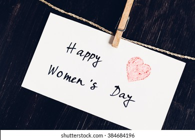 Send a Happy Women's Day greeting message on bright white paper with red heart against a dark wooden background for International Women's Day, March 8.