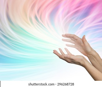 Sending distant healing energy - Female outstretched healing hands appearing to send energy out on a flowing rainbow colored  vivid whooshing energy formation background