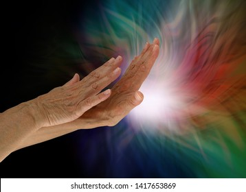 Sending light and healing energy out where it is needed - female hands appearing to push out white light from the palm with darkness on left and multiple colours around the light source